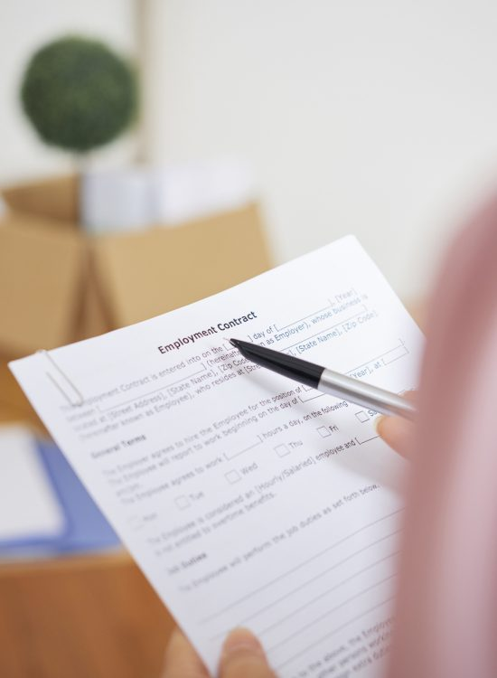 Close-up image of businesswoman reading employment contract and checking details